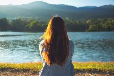 Chica sentada sola frente a un lago representando la tristeza